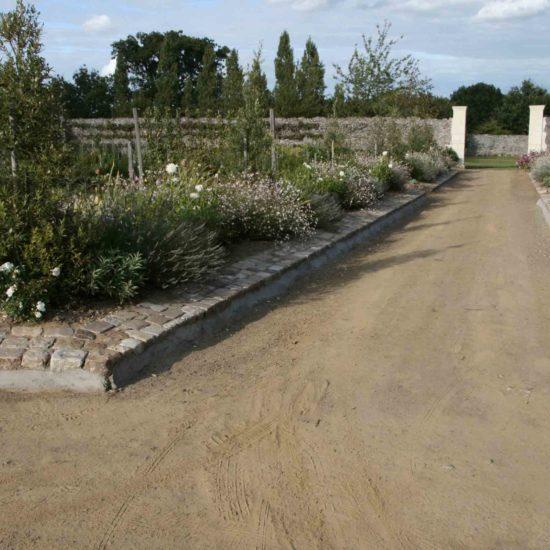 Photos du jardin potager de La Baronnière : le thème gris et blanc depuis l'allée centrale et le verger à gauche